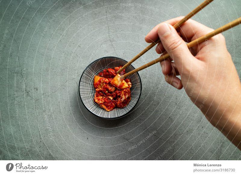 Man's hand using chopsticks to take Kimchi. Korean cuisine. Vegetable Nutrition Lunch Dinner Vegetarian diet Asian Food Bowl Fresh Healthy Hot Delicious Gray