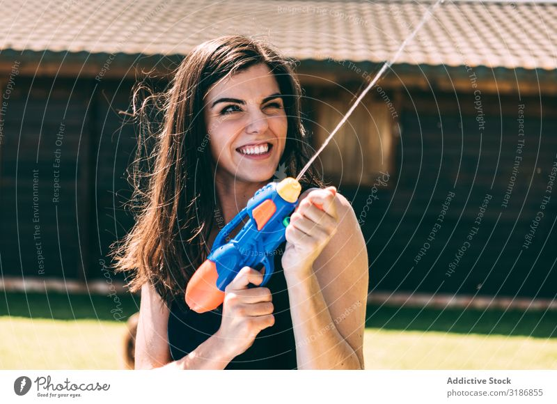 Young woman shooting and splashing with water gun Woman Splashing Water Youth (Young adults) Aim water-pistol Happy Joy Summer Beautiful Playing Party Wet Girl