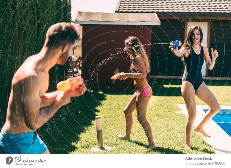Friends splashing with water guns Friendship Splash Water poolside Man Woman Joy Summer Happy Leisure and hobbies Youth (Young adults) Splashing Swimming pool