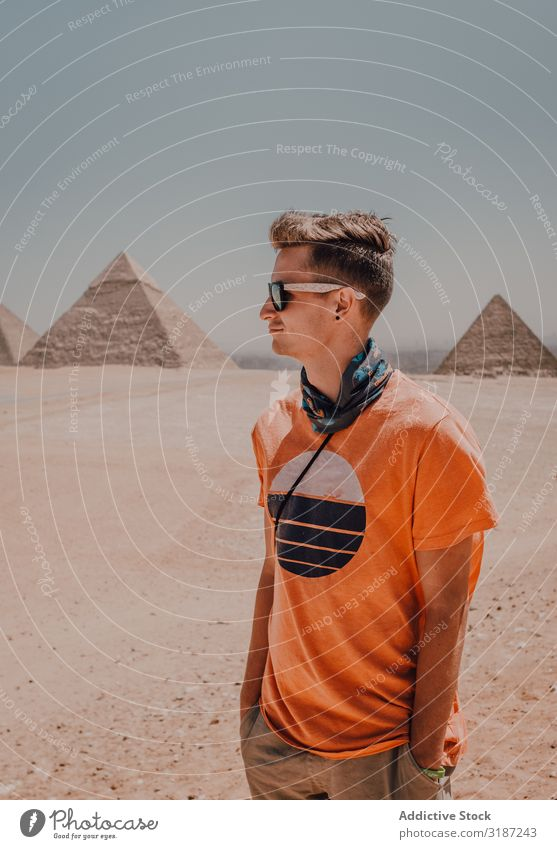 Young man against Great Pyramids traveler Egypt Man Giza Cairo Youth (Young adults) Desert Looking away Famous building Sky Beautiful weather Trip Tourism