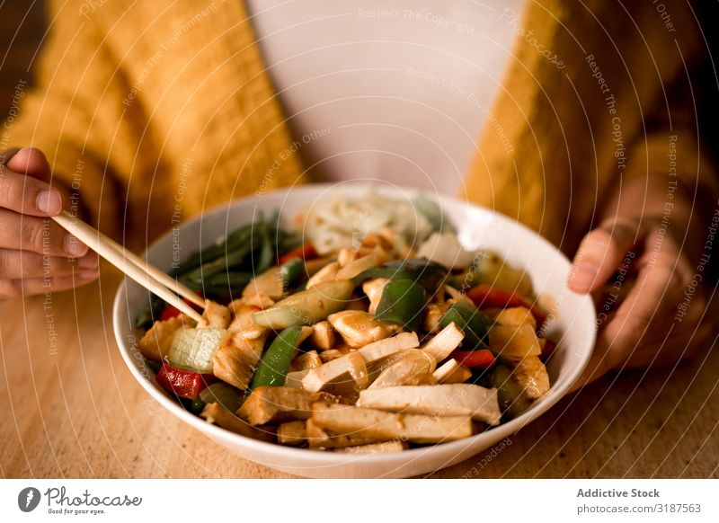 Female eating bowl of cooked appetizing diet dish Food Vegetarian diet Vegetable Carrot Onion Mushroom Chopstick Bowl