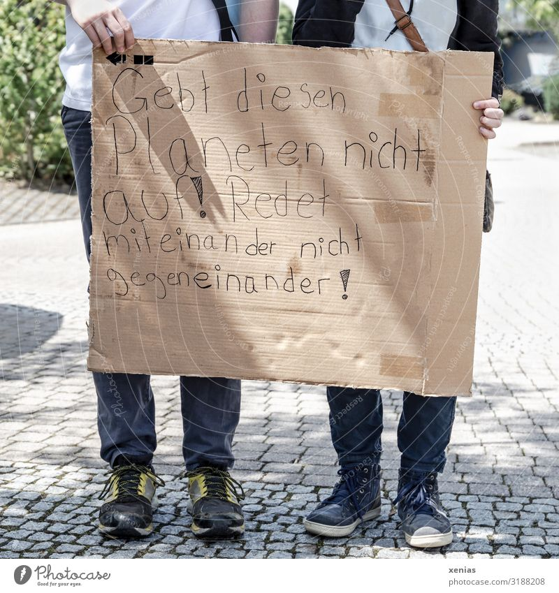 Weltschmerz / two teenagers stand on the street and hold labeled cardboard in their hands for fridays for future - Demonstration - Don't give up on this planet! Do not talk to each other against each other!