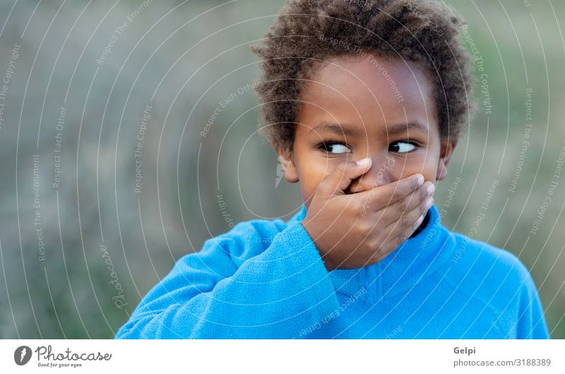 Little african boy covering his mouth with a blue jersey Happy Beautiful Face Calm Child Schoolchild Human being Boy (child) Man Adults Infancy Mouth Lips Hand