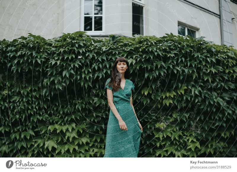 woman wearing an elegant green dress is standing in front of hedge adult attractive beautiful woman charming chic city classic clothing confident europe