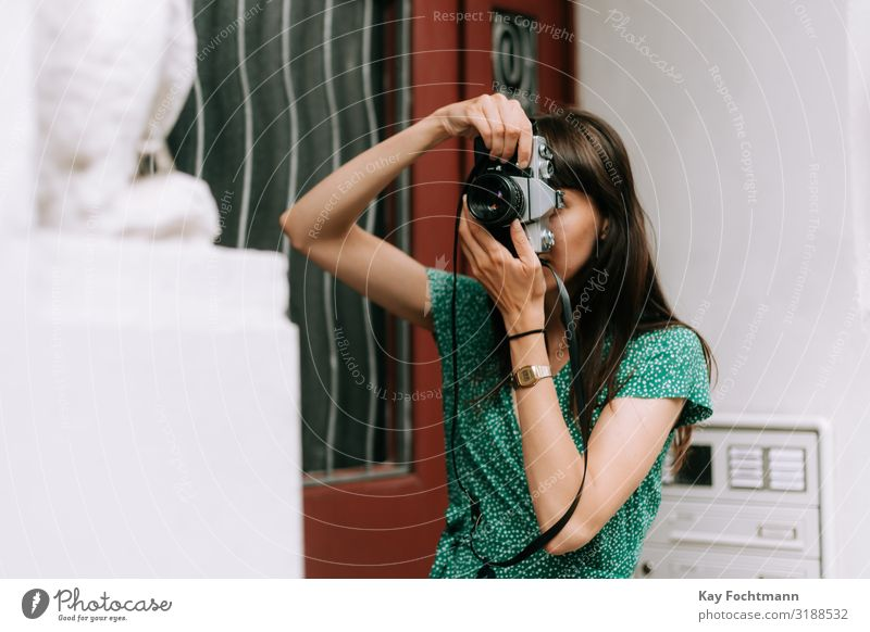 elegant woman wearing a green dress is taking a picture with an old film camera activity analog beauty capturing caucasian discovering elegance european explore
