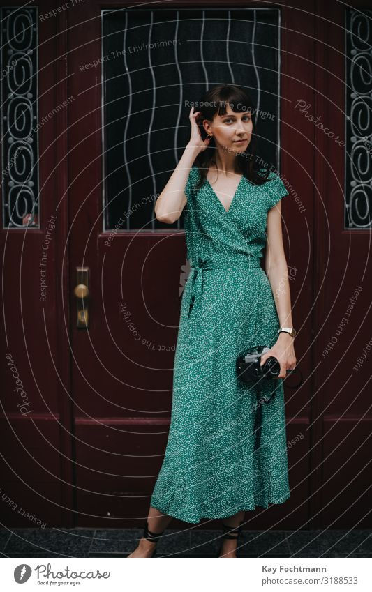 elegant woman wearing a green dress is holding an old film camera in her hands activity analog beauty capturing caucasian discovering elegance european explore