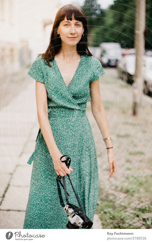 elegant woman wearing a green dress is walking with an old film camera in her hand activity analog beauty capturing caucasian discovering european explore