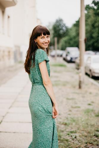 woman wearing an elegant green dress is turning around to smile at camera adult attractive beautiful woman charming chic city classic clothing confident europe