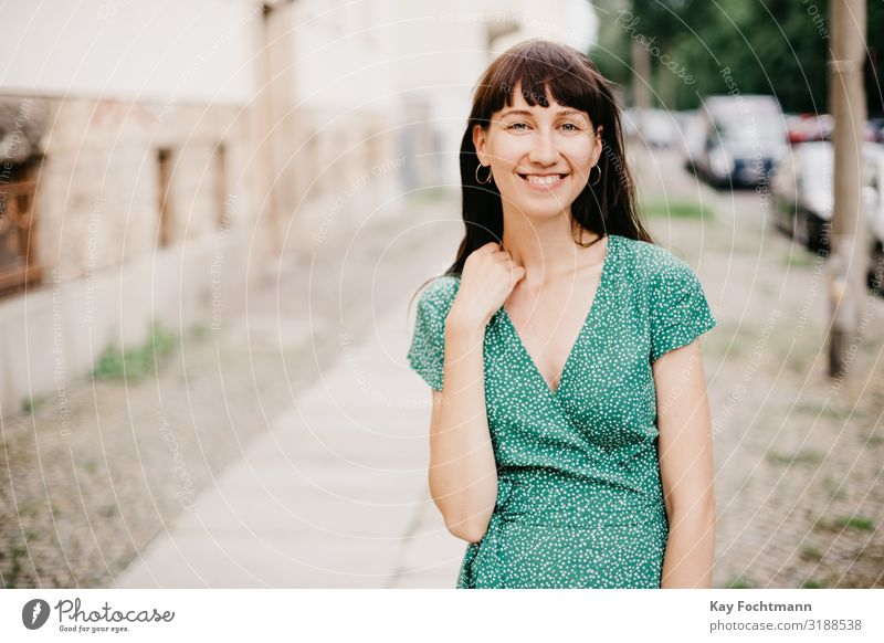 woman wearing an elegant green dress is smiling into camera adult attractive beautiful woman charming chic city classic clothing confident europe european