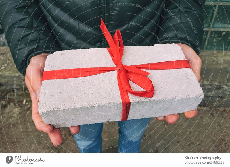 White brick with red ribbon as gift box Lifestyle Shopping Design Joy Leisure and hobbies Decoration Christmas & Advent Birthday Hand 1 Human being Package Box