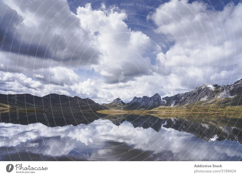 Cloudy sky over calm lake and mountains Lake Mountain Clouds Sky Calm embalse del casares Spain Léon Reflection Landscape Nature Deserted Basin Pond Weather