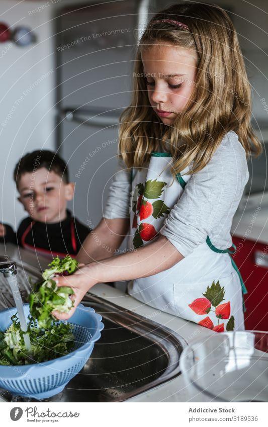 Child washing herbs for salad Girl Washing Hand Herbs Water Sink Spigot Fresh Salad Cooking Mature Healthy Vegan diet Vegetarian diet Clean Organic Natural