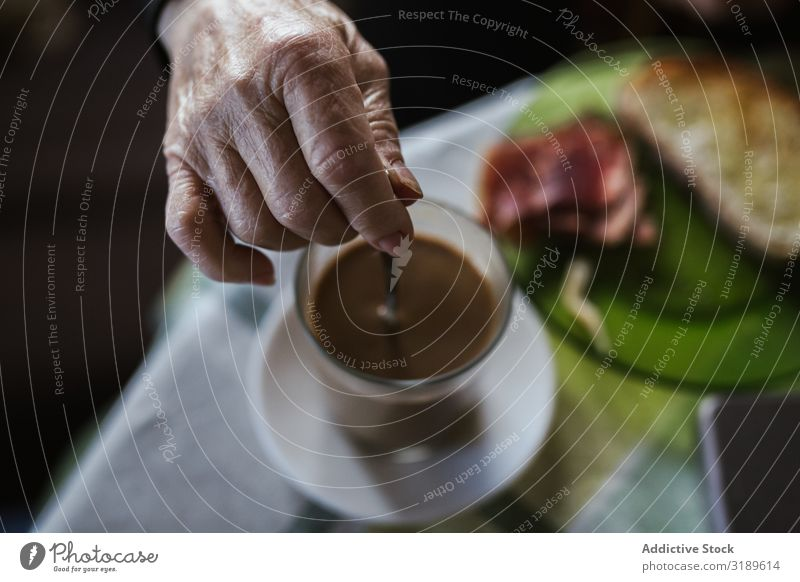 Hand of aged woman holding spoon in cup Stir Coffee Spoon Old Drinking Breakfast Beverage Cup Hot Food Morning Human being Woman Senior citizen Table Aromatic