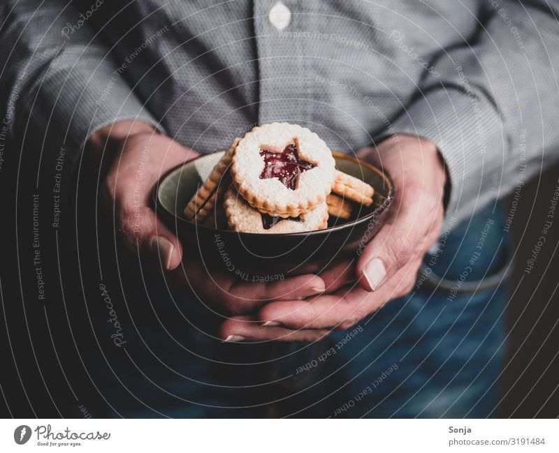 Man holding Christmas cookies in a bowl in his hands Food Dough Baked goods Cookie Christmas biscuit To have a coffee Bowl Lifestyle Christmas & Advent