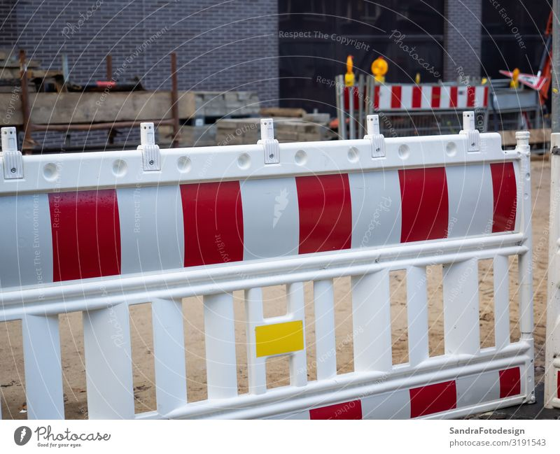A red white barrier of a construction site in the city Construction machinery Industrial plant Manmade structures Architecture Wall (barrier) Wall (building)