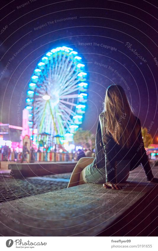 Young woman contemplating a Ferris wheel at night Joy Vacation & Travel Night life Entertainment Party Event Music Feasts & Celebrations Feminine