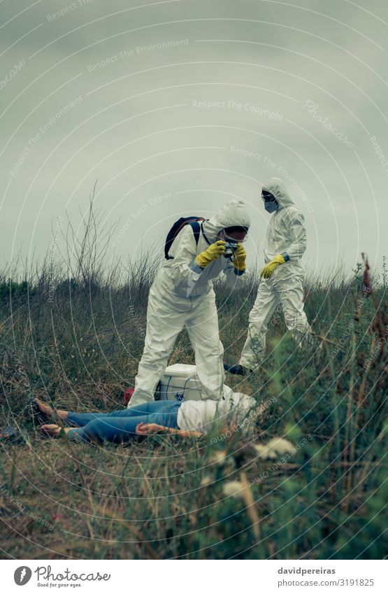 Man and woman in protective suit taking a photo of a corpse Body Camera Human being Woman Adults Protection Death Dangerous Take Illustration Corpse Epidemic