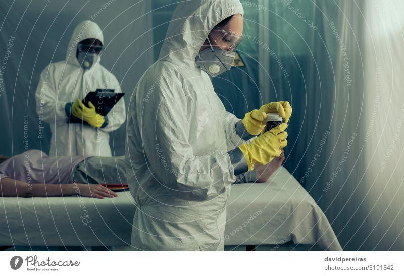 Doctors preparing medication for sick woman Medical treatment Illness Medication Human being Woman Adults Man Gloves Lie Epidemic medicine flask field hospital