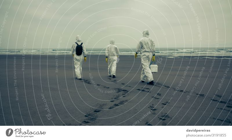 People with protection suits walking on the beach Beach Ocean Waves Human being Woman Adults Man Sand Coast Gloves Footprint Protection Crisis Unrecognizable