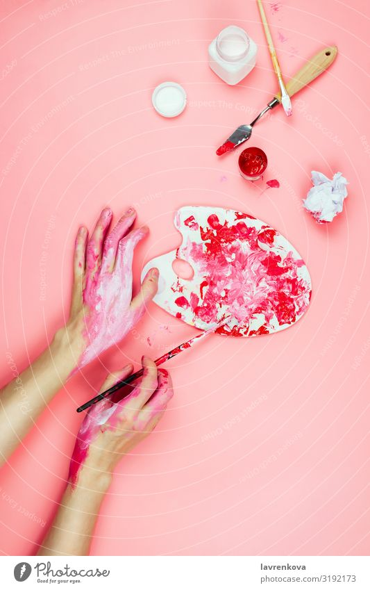 Woman's hands covered in paint and artist's supplies on pink Drawing Design Adults Artist Body Brush Conceptual design Creativity Painting and drawing (object)