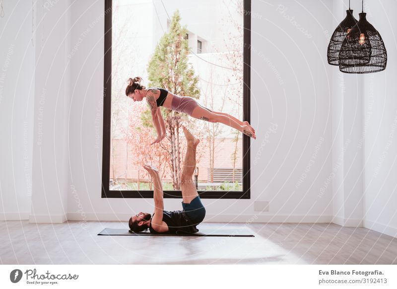 young couple Couple practicing acro yoga by the window in studio or gym. Healthy lifestyle Yoga Sports Gymnasium Man Power Human being