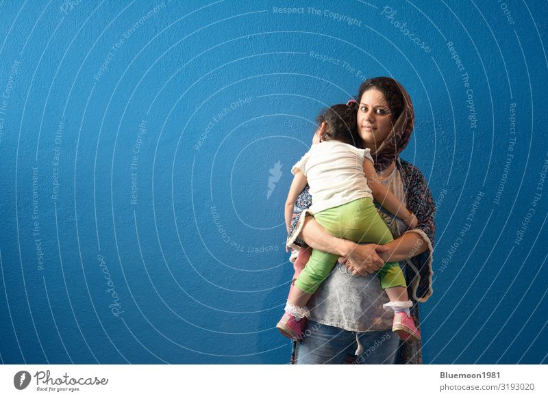 Muslim mother embraced slept little girl in front of blue wall background Lifestyle Beautiful Relaxation Interior design Child Human being Feminine Young woman