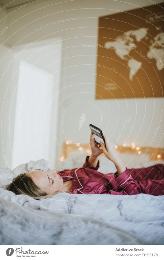 Woman lying down on bed with smartphone Day pajamas Morning Bed Loneliness freelance Youth (Young adults) device Freedom Tablet computer White Positive Wake Lie