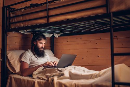 Man using laptop in rustic bunk bed Notebook Rustic Hipster Work and employment freelance bearded Wood House (Residential Structure) concentrated Technology