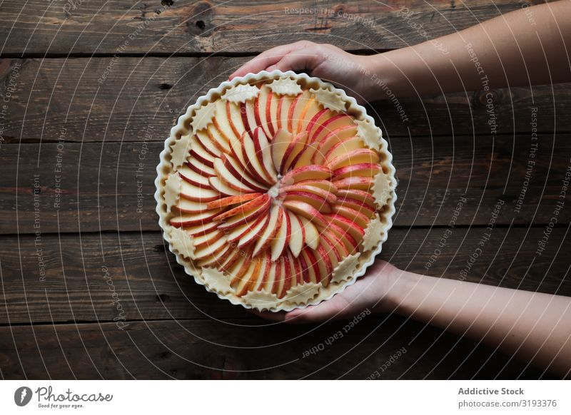 unrecognizable woman showing a tasty apple pie on a wooden table Pie Apple Fresh Wood Rustic Window Home-made Day Brown Confectionary Organic parchment Warmth