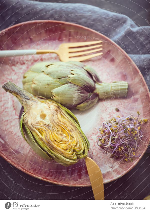 Knife fork and artichokes on plate Artichoke Knives Fork Plate Cut whole Table Food Cooking Organic Healthy Fresh Diet Nutrition Vegan diet Vegetarian diet