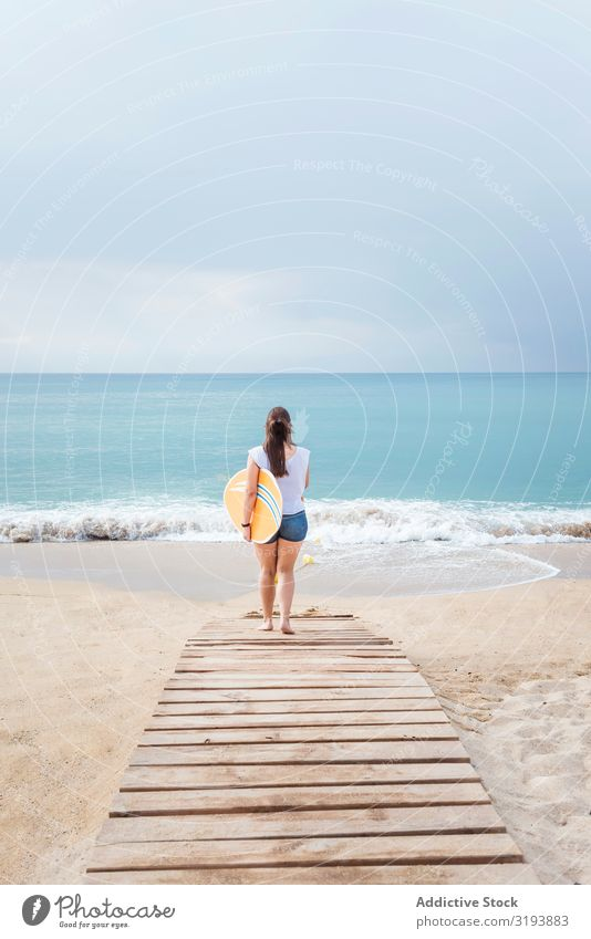 Back view of a teenage girl walking on the beach to seashore while holding a surfboard Surfboard Sports Walking Aquatics Surfing Stand Beach Surfer Ocean Woman