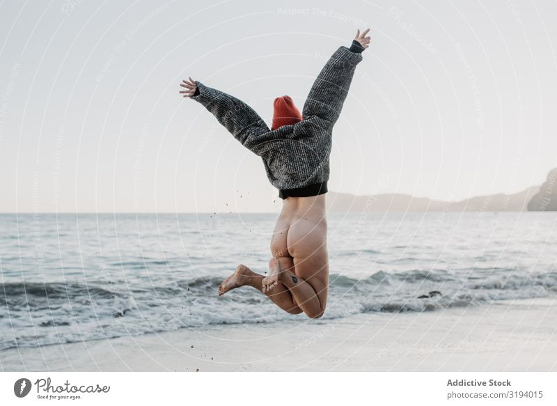 Unrecognizable woman enjoying freedom near waving sea Woman Jump Ocean Freedom Waves Bottom raised Hands up! Storm Nature Water Naked Sweater Hat Beach Coast