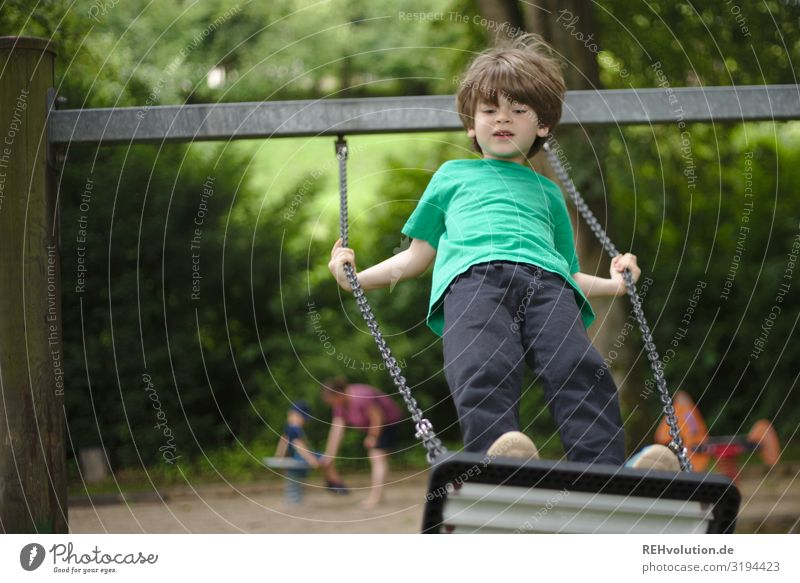 Child swinging on a playground Authentic naturally Boy (child) Summer fun Happy Joy Swing To swing Playing Infancy Playground swinging is like flying