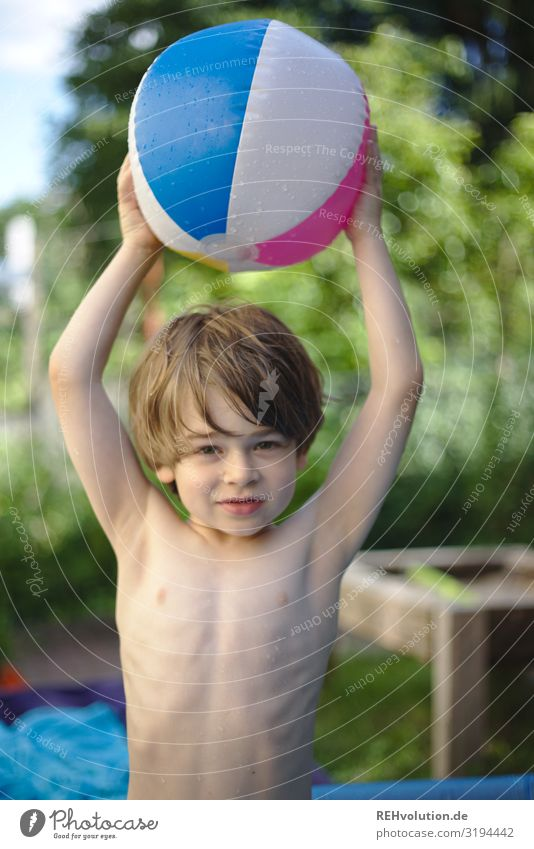 Child holds a water polo ball in the garden Ball Beach ball Garden Wet Boy (child) Infancy fortunate luck Joy Summer warm stop Throw Playing variegated