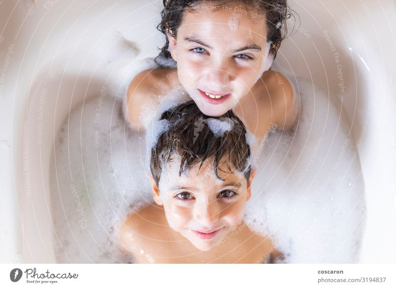 Two kids taking a bath looking a camera Lifestyle Joy Happy Beautiful Personal hygiene Body Skin Well-being Swimming & Bathing Bathtub Bathroom Child