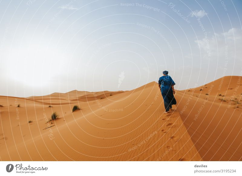 Arabian man in blue clothes walking on a desert dune. Lifestyle Exotic Vacation & Travel Tourism Trip Adventure Expedition Sun Human being Man Adults 1