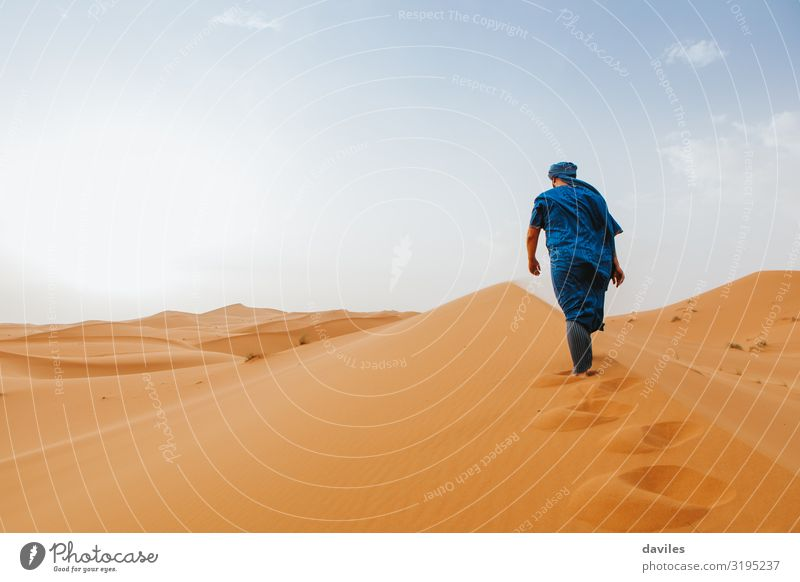 Arabian man in blue clothes walking on a desert dune. Lifestyle Vacation & Travel Tourism Trip Adventure Expedition Human being Man Adults 1 18 - 30 years
