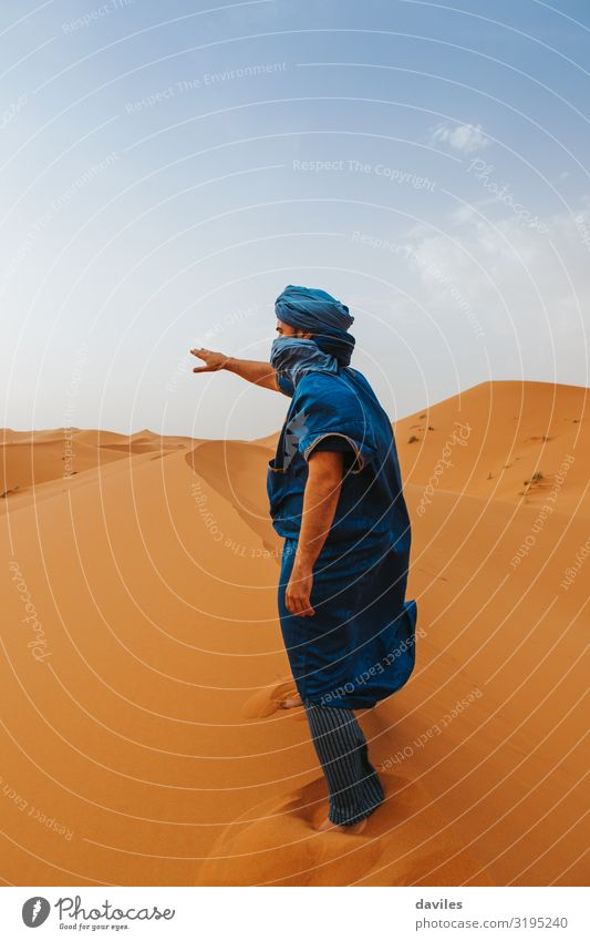Arabian man in blue clothes walking on a desert dune. Lifestyle Vacation & Travel Tourism Trip Adventure Human being Man Adults 1 18 - 30 years