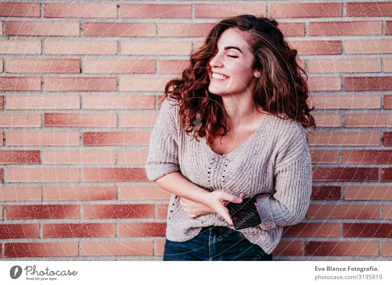 young woman using mobile phone outdoors at the city Youth (Young adults) Woman Cellphone Technology Internet City Town Wall (building) Brick Smiling Happy