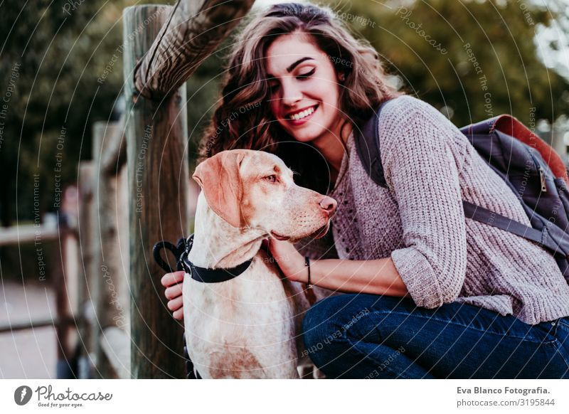 young woman and her dog outdoors in a park with a lake. sunny day, autumn season Portrait photograph Woman Dog Park Youth (Young adults) Exterior shot Love Pet