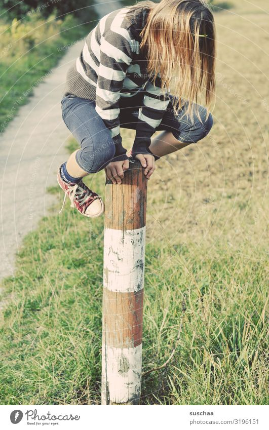 climber Child Girl boyish Climbing Playing Reckless Pole Wooden stake Fence post To hold on Exterior shot Footpath Nature Romp Infancy Dexterity Lanes & trails