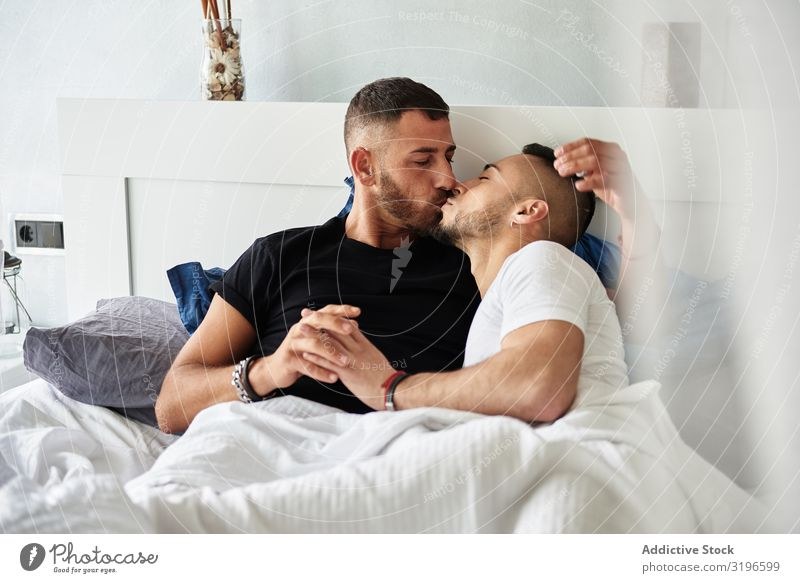 Smiling gay couple hugging and kissing on bed Couple Homosexual Embrace Relationship Kissing homo Affection enjoyment Happy Love lgbt Together