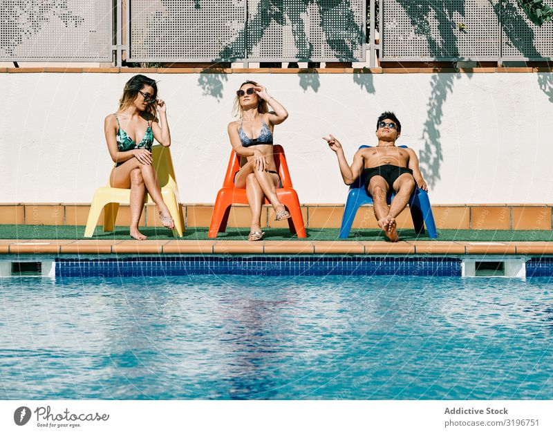 two young and beautiful women looking at a handsome man by the pool Lifestyle diversity Chinese Caucasian Asia Model Russian latina Summer Happy To enjoy Joy