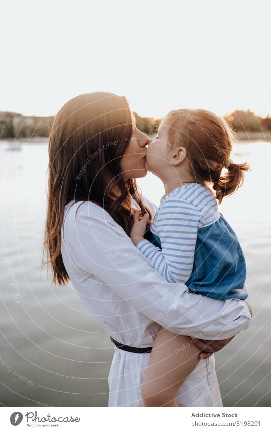 Mother and daughter standing near water Daughter Water Coast Park embracing Carrying Evening Lifestyle Leisure and hobbies Woman Girl Child Love tender River