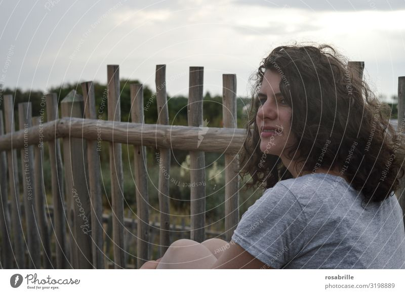 young pretty brunette woman with curly hair sits pensively in front of a board fence in the dunes near the beach and looks into the distance youthful Brunette