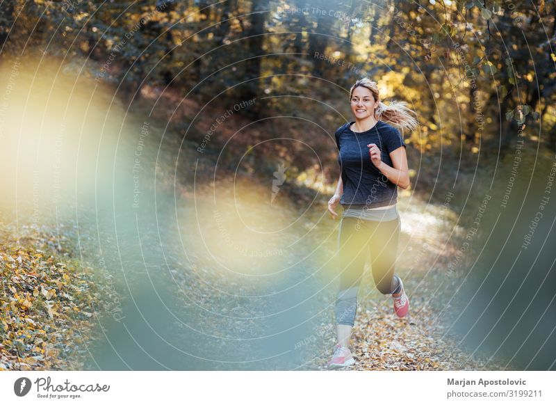 Young sporty woman running in the woods in autumn Healthy Athletic Fitness Life Sports Sports Training Track and Field Sportsperson Jogging Feminine Young woman