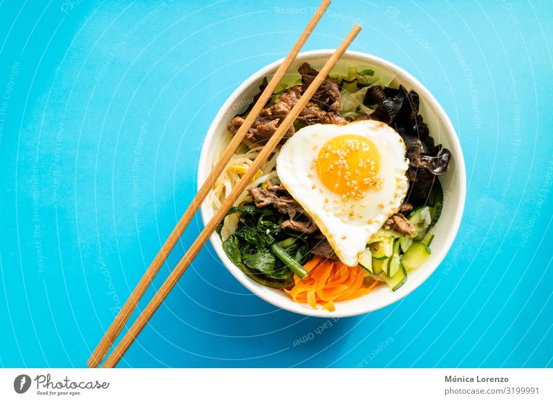 Bibimbap with beef, egg and vegetables. Korean cuisine. Meat Vegetable Bowl Delicious Blue Pink Tradition nori cooking pepper Dish chili bibim soy sprouts