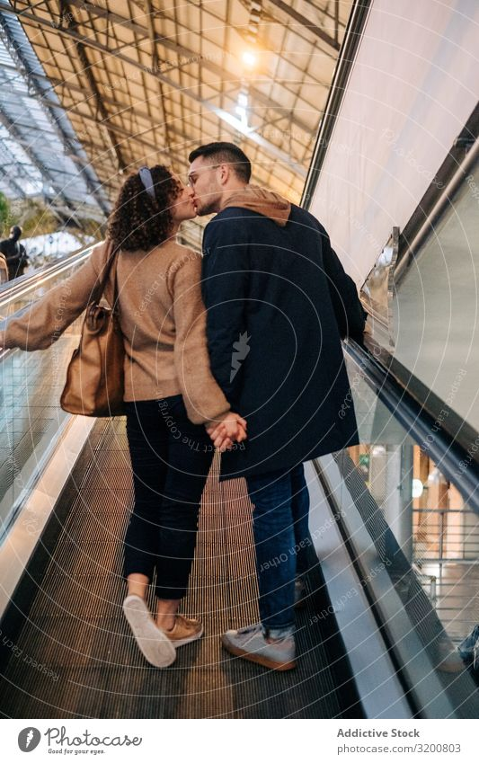 Young couple kissing riding travelator in mall Couple Moving pavement Mall holding hands Date Youth (Young adults) Together Illumination Lifestyle