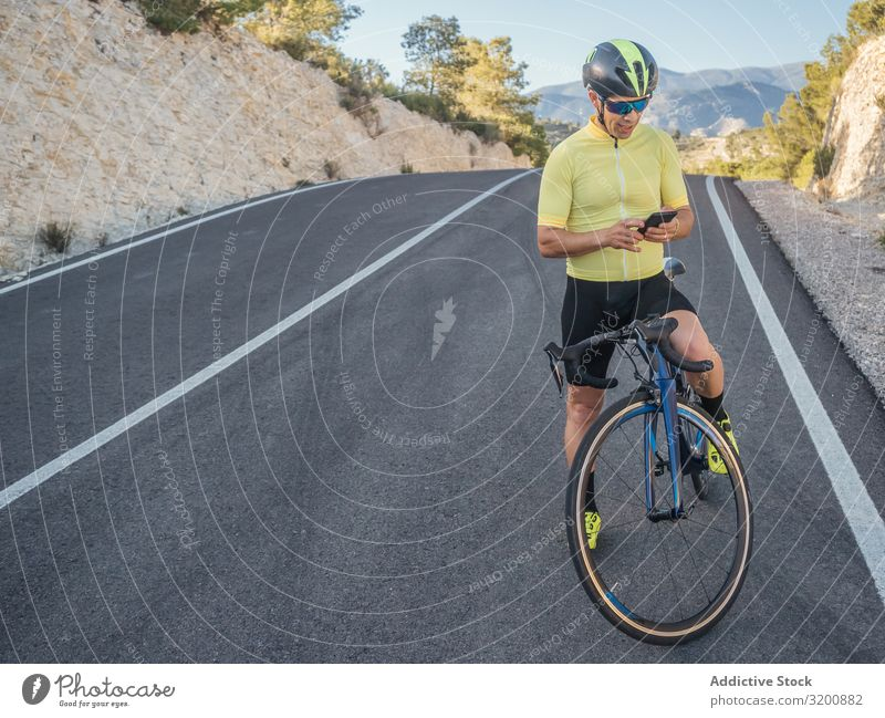 healthy man with smartphone after cycling in a mountain road in a sunny day Leisure and hobbies Athlete Sports Ride Bicycle Racing sports Man Motorcycling