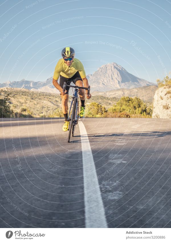 healthy man riding a bicycle on a mountain road in a sunny day Leisure and hobbies Athlete Sports Ride Bicycle Racing sports Man Motorcycling Exterior shot